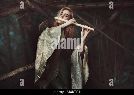 La princesse des elfes jouant de la flûte . Romantisme et fantaisie Photo Stock