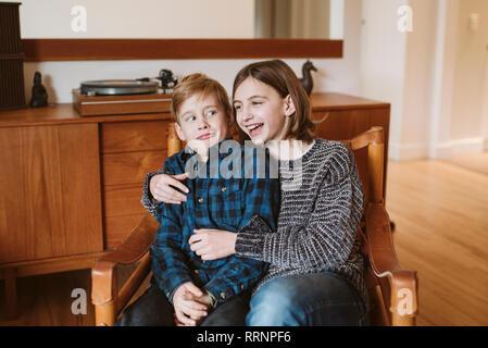 Riant Portrait sœur serrant frère making a face Photo Stock