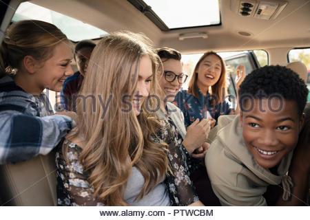 Les adolescents ludique pilling en voiture Photo Stock