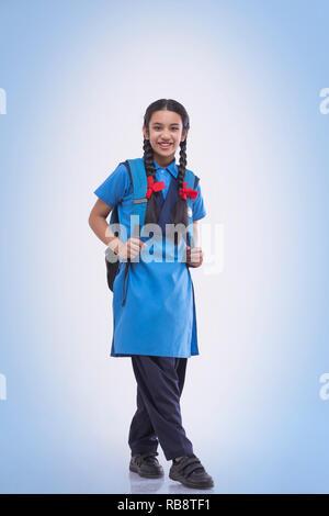 Portrait de jeune fille en uniforme scolaire livre sac et portefeuille Photo Stock