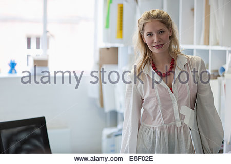 Smiling architect holding plans dans office Photo Stock