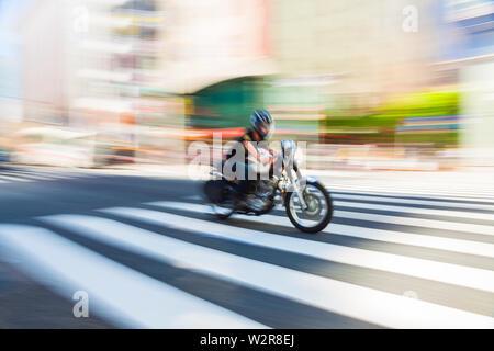 Motion blurred shot d'une moto à la vitesse sur un passage pour piétons à Tokyo, Japon. Photo Stock