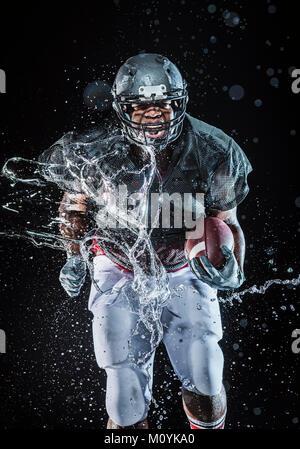 Les éclaboussures d'eau sur le joueur de football noir tournant Photo Stock