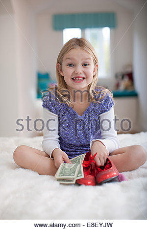 Smiling girl holding dollar bills Photo Stock