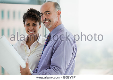 Business people reading blueprints in office Photo Stock