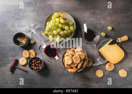 Snack-vin. Le fromage, raisins, noix, fromage craquelins Biscuits, d'abeilles avec une verre de vin rouge et sombre à couteau sur fond de texture. Mise à plat, Photo Stock