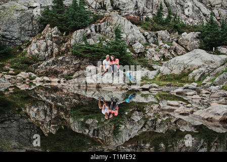 Portrait couple hiking, reposant à Rocky Mountain Lake, chien, BC, Canada Photo Stock