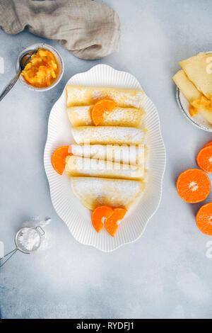 Crêpes sans gluten servi dans une assiette ovale blanc, garni de tranches d'orange et du sucre en poudre, accompagnés de confiture d'orange, mini-tamis et coupées en deux Photo Stock