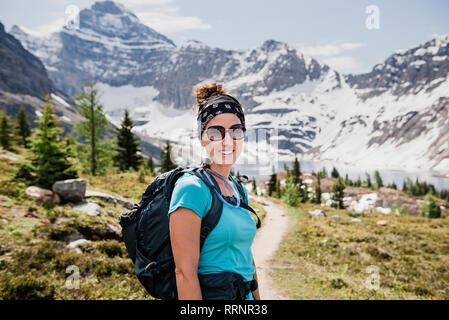 Portrait confident female hiker on sunny, sentier de montagne idyllique, Parc national Yoho, Colombie-Britannique, Canada Photo Stock