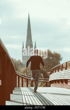 Homme qui court à travers le pont urbain avec l'église en arrière-plan Photo Stock
