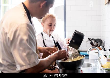 Le chef des hommes et des femmes portant des tabliers brun debout à comptoir de la cuisine, faire la sauce hollandaise. Photo Stock