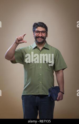 Smiling man wearing eyeglasses tenant un petit sac dans une main et de tenir un geste montrant produit avec les doigts. Photo Stock