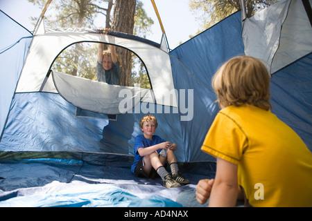 Deux jeunes garçons assis dans une tente vide Photo Stock