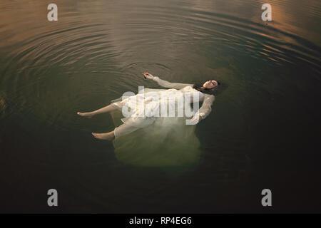 Jeune femme gisant mort dans les eaux des lacs Photo Stock