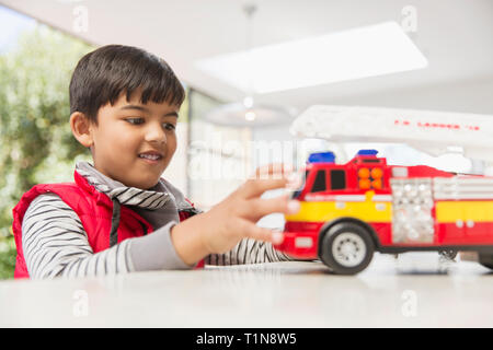 Boy Playing with fire engine toy Photo Stock