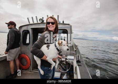 Portrait of smiling woman with dog sur bateau de pêche Photo Stock