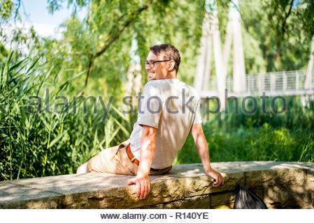 Vue arrière d'un homme assis par des arbres Photo Stock