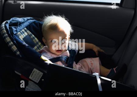 Un bébé assis dans un siège de voiture Photo Stock