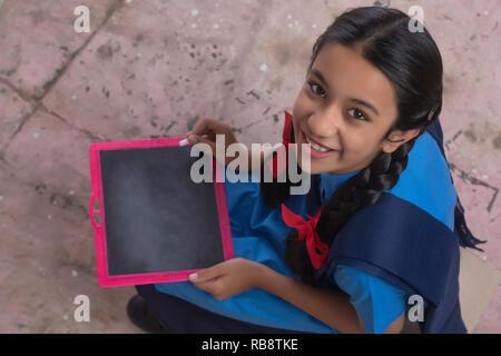 Close up of rural school girl écrit sur l'ardoise Photo Stock