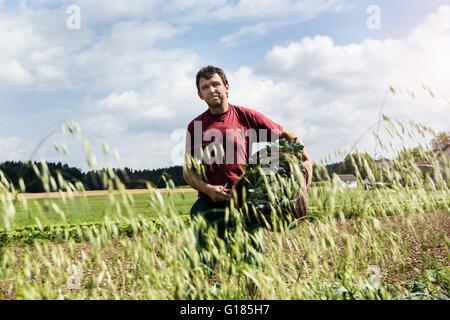 Agriculteur exerçant son panier plein de légumes dans une ferme biologique Photo Stock