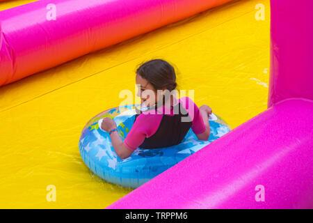 Girl on inflatable ring s'amusant sur le toboggan géant, toboggan, à Bournemouth, Dorset UK en Juin Photo Stock