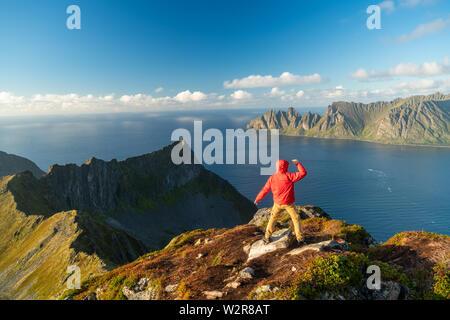 Man with arms répartis sur au sommet de la montagne, l'île de Senja, Troms Photo Stock