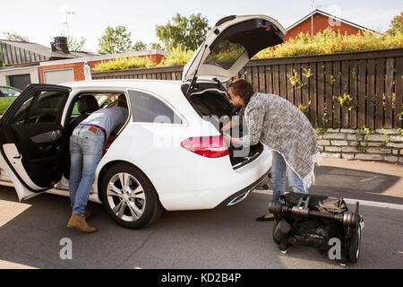 L'homme et la femme l'emballage assurance en voiture Photo Stock