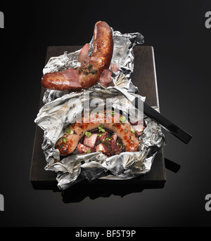 Saucisses grillées et oignons rouges assaisonnés et cuits dans du papier d'aluminium, sur un fond Photo Stock