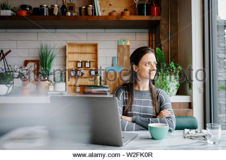 Confiant, thoughtful woman working at laptop, looking out window in cafe Photo Stock