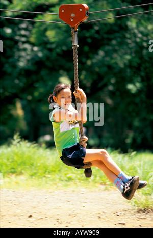 Fille jouant avec l'équipement de jeux dans le parc Photo Stock