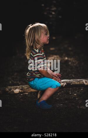 Enfant assis sur un journal Photo Stock
