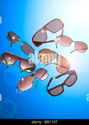 Une collection de lunettes de soleil sur un fond bleu Photo Stock