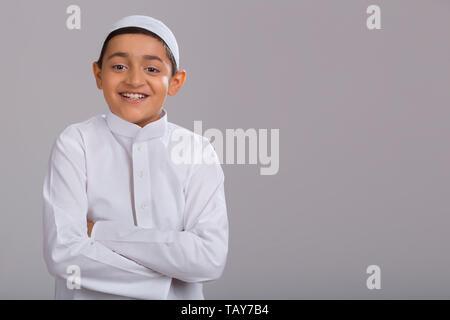 Jeune garçon musulman wearing cap avec les mains pliées et souriant Photo Stock