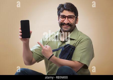 Smiling man wearing eyeglasses pointe vers un téléphone mobile qui a lieu dans d'autres part. Photo Stock