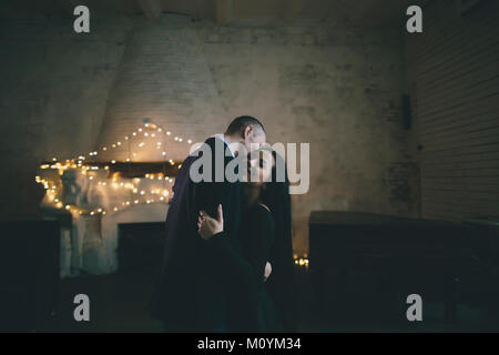 Caucasian couple hugging près de cheminée Photo Stock