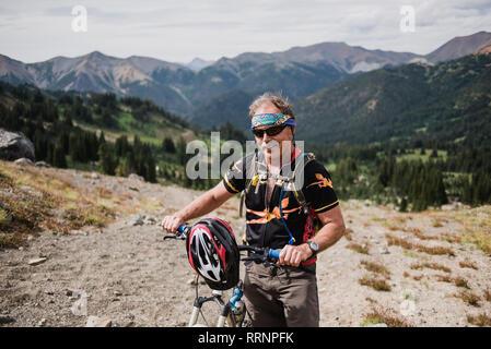 Portrait senior man mountain biking in remote, paysage Montagnes Chilcotin, en Colombie-Britannique, Canada Photo Stock