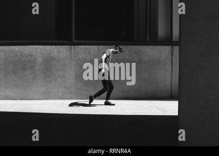 Ombre suit homme marchant sur la chaussée ensoleillé Photo Stock