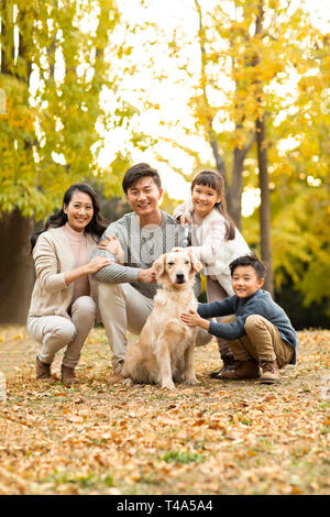 Heureux jeune famille avec chien dans les bois d'automne Photo Stock