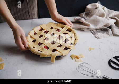 Tarte aux fruits crus un treillis décoration sur le haut. Arrière-plan de béton, processus de cuisson. Photo Stock