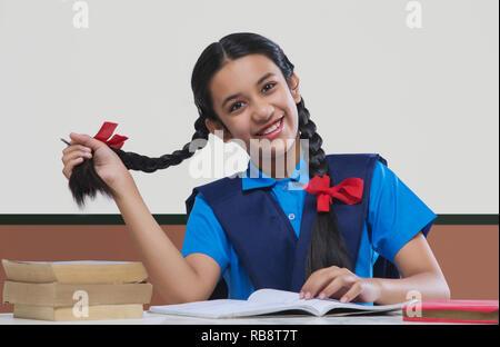 Fille dans l'uniforme scolaire en jouant avec ses cheveux tout en étudiant à la table Photo Stock