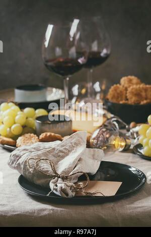 Accueil dîner table set avec vin, assiette de fromage, apéritifs et vide la plaque avec une serviette en tissu. Photo Stock
