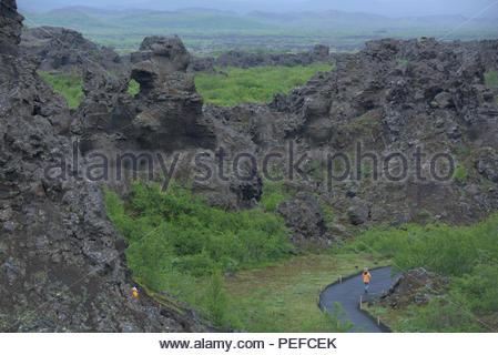 Un randonneur passe devant les formations de lave Dimmuborgir. Photo Stock