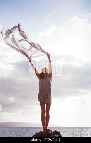Femme debout sur un rocher près de l'océan, tissu holding dans le vent. Photo Stock