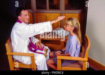 Prêtre catholique bénédiction enfant avec plus de main tête de l'enfant au cours de la réconciliation. © Myrleen ....Pearson Ferguson Cate Photo Stock
