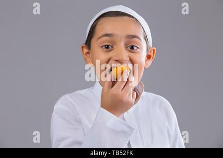 Jeune garçon musulman wearing cap de sourire et de manger des douceurs Photo Stock