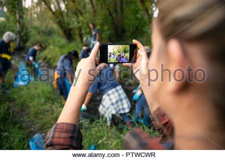 Femme avec téléphone appareil photo photographier bénévoles, le nettoyage des ordures dans park Photo Stock