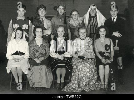 Une photographie montrant de jeunes hommes et femmes dans une variété de fantaisie, y compris une dame Victorienne, un Pierrot, un cheikh et d'une énigmatique jeune homme portant un kilt avec le pinceau et sock rangement bretelles. Date: Photo Stock