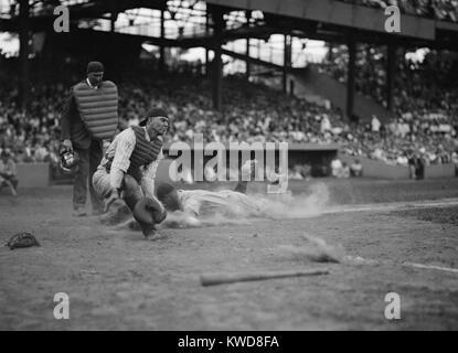 Lou Gehrig des Yankees notes comme Joe Harris' jeter s'éloigne de catcher Hank Severeid des sénateurs. Photo Stock