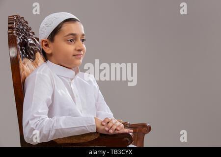 Jeune garçon musulman wearing cap assis sur la chaise et à l'écart Photo Stock