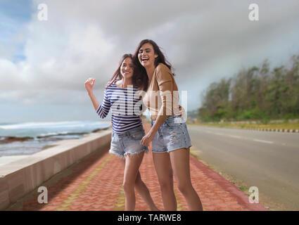 Deux femmes marchant ensemble sur la mer à côté de la route Photo Stock